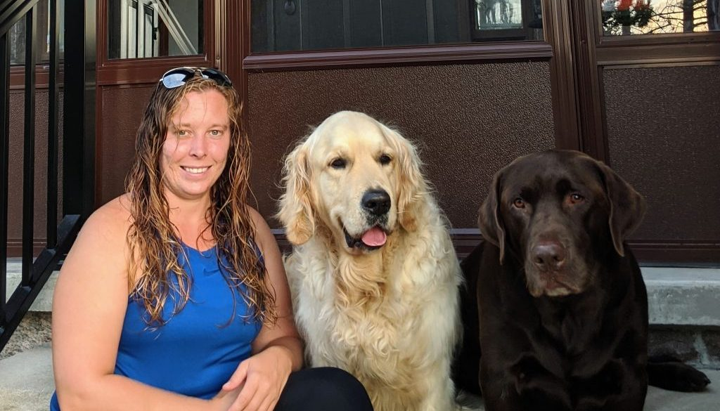 Ashley Graham sitting on her porch with her two dogs a blonde retriever and chocolate lab